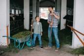 Fotografie Vater und Sohn halten Mistgabeln und lächelnd einander während der Arbeit zusammen im stall