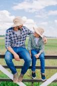 Fotografie Šťastný otec a syn v panama klobouky sedí na plotě a vzájemně se usmívá na farmě