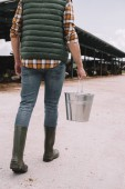 Fotografie cropped shot of farmer in rubber boots holding bucket and walking in cowshed