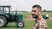 Fotografie side view of handsome middle aged farmer smiling while standing near tractor in field