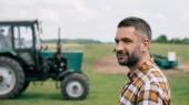 Közép-szép oldalnézetből éves mezőgazdasági traktor területén közel állva mosolyogva
