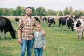 otec a syn se usmívá na kameru při stojící poblíž pastvy dobytka na farmě