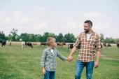 Fotografie glücklicher Vater und Sohn Hand in Hand und lächeln einander auf der farm