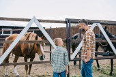 back view of father and son smiling each other while standing near horses at ranch