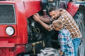 Fotografie Šťastný otec a syn, opravy motor traktoru dohromady