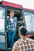 Fotografie back view of father looking at happy son standing in tractor