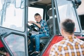 Fotografie selective focus of father looking at happy son sitting in tractor