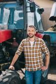 szép középső éves mezőgazdasági traktor közelében állt, és mosolyogva kamera
