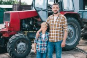 Fotografie happy father and son in checkered shirts smiling at camera while standing together neat tractor at farm