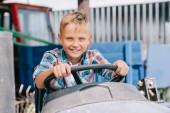 Fotografia bambino felice equitazione veicolo agricolo e sorride alla macchina fotografica