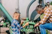 Fotografie otec a syn spolu opravy zemědělských vozidel