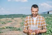 Fotografia bello sorridente contadino utilizzando la tavoletta digitale mentre levandosi in piedi sul campo