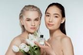 krásné nahé multikulturní ženy představují s tulipány a parfém, izolované Grey