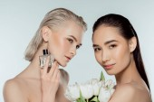 naked multiethnic girls posing with tulip flowers and bottle of perfume, isolated on grey