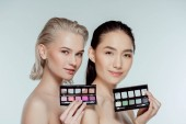 multiethnic naked women posing with palettes of eyeshadows, isolated on grey