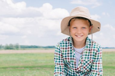 Adorable child in panama hat smiling at camera on farm stock vector