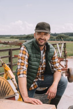 handsome middle aged farmer in cap smiling at camera while working at ranch
