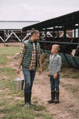 father with bucket and little son in rubber boots looking at each other while working together at ranch