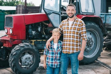 happy father and son in checkered shirts smiling at camera while standing together neat tractor at farm