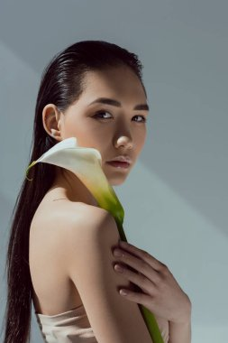attractive asian woman with calla flower, isolated on grey