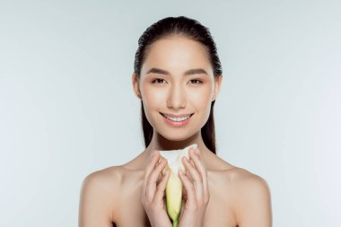 happy attractive asian girl with calla flower, isolated on grey
