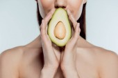 cropped view of naked girl posing with natural avocado, isolated on grey