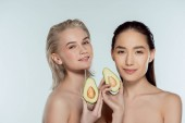 Fotografie multiethnic naked girls posing with two halves of avocado, isolated on grey, skin care concept
