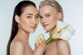Fotografie beautiful multicultural naked girls posing with avocado and calla flowers, isolated on grey, skin care concept