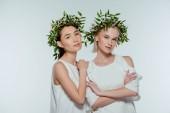 atraktivní mnohonárodnostní dívky pózuje v bílé šaty a květinové věnce, izolované na šedé, přírodní krásy