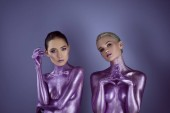 Fotografie attractive multicultural girls in purple glitter posing for fashion shoot, isolated on violet