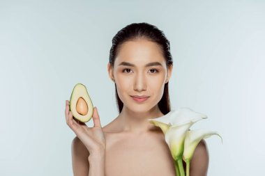 beautiful asian girl posing with avocado and calla flowers, isolated on grey