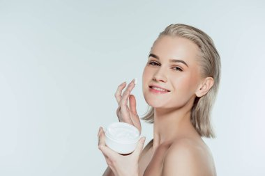 Happly woman applying face cream, isolated on grey stock vector