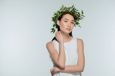 beautiful asian girl posing in floral wreath, isolated on grey