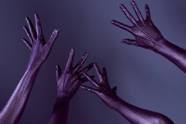 partial view of female hands in ultra violet glitter, isolated on purple