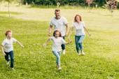šťastná rodina s dvěma dětmi, baví a běží spolu v parku
