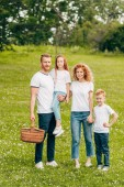 Fotografie happy family smiling at camera while standing with picnic basket in park