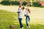 šťastní rodiče objímání rozkošné děti na pikniku v parku