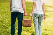 Fotografie oříznutý snímek mladého páru drží piknikový koš a procházky v parku
