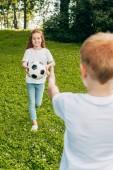 Fényképek vágott lövés a bátyám és a húgom játszik a futball-labda park