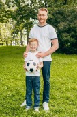 Fotografie happy father and son with soccer ball standing together and smiling at camera in park