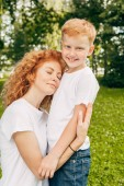 happy young mother hugging adorable little son in park