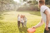Fotografia famiglia felice di redhead che gioca con disco al parco di volo