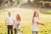 Fotografia bambino felice che gioca con il disco mentre madre e fratello di riposo dietro nel parco di volo