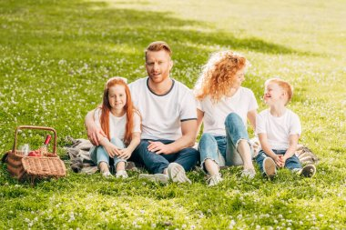happy family with two children sitting together at picnic in park