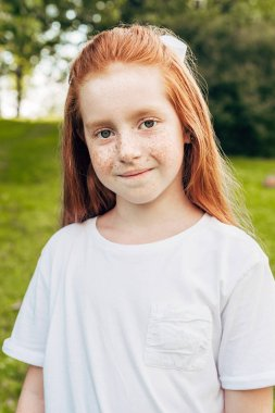 portrait of adorable red haired child smiling at camera in park