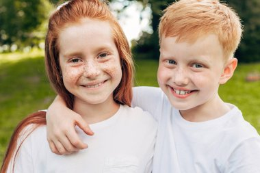 beautiful happy redhead siblings embracing and smiling at camera in park