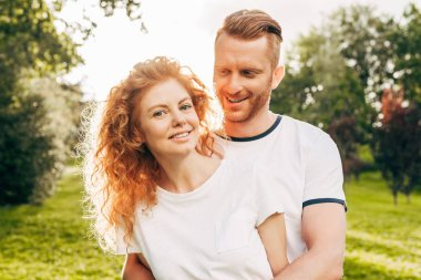 beautiful happy redhead couple spending time together in park