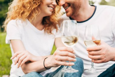 cropped shot of happy couple holding glasses of wine in park