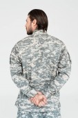 back view of male soldier in camouflage clothing isolated on grey