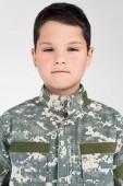 Fotografia Ritratto di bambino in uniforme militare rivolto verso lobiettivo su priorità bassa grigia